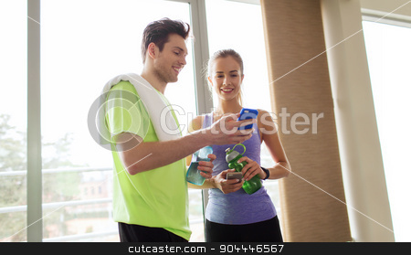 happy woman and trainer showing smartphone in gym stock photo, fitness, sport, technology and slimming concept - smiling young woman and personal trainer with smartphone and water bottles in gym by Syda Productions