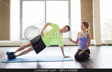 man and woman doing plank exercise on mat in gym stock photo, fitness, sport, technology and people concept - man and woman with smartphone doing side plank exercise on mat in gym by Syda Productions
