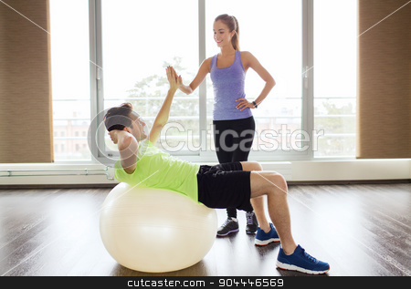 smiling man and woman with exercise ball in gym stock photo, sport, fitness, lifestyle and people concept - smiling man and woman flexing muscles with exercise ball in gym by Syda Productions