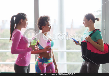happy women with bottles of water in gym stock photo, fitness, sport, training and lifestyle concept - group of happy women with bottles of water, smartphone and bag talking in gym by Syda Productions