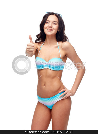 happy woman in swimsuit showing thumbs up stock photo, people, fashion, swimwear, summer and beach concept - happy young woman in bikini swimsuit showing thumbs up gesture by Syda Productions