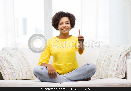 happy african american young woman at home stock photo, people, ethnicity, gesture and leisure concept - happy african american young woman showing thumbs up and sitting on sofa at home by Syda Productions