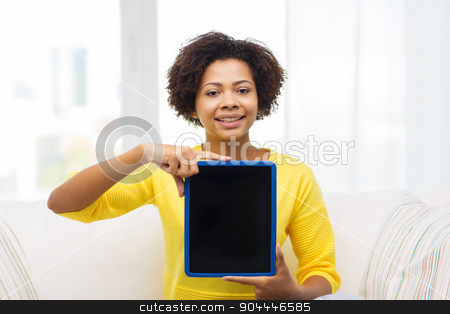 happy african american woman with tablet pc stock photo, people, technology, advertisement and leisure concept - happy african american young woman sitting on sofa and showing tablet pc computer black blank screen at home by Syda Productions