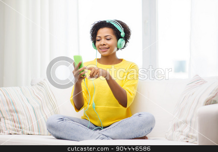 happy african woman with smartphone and headphones stock photo, people, technology and leisure concept - happy african american young woman sitting on sofa with smartphone and headphones listening to music at home by Syda Productions