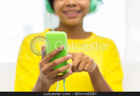 happy african woman with smartphone and headphones stock photo, people, technology and leisure concept - close up of happy african american young woman sitting on sofa with smartphone and headphones listening to music at home by Syda Productions