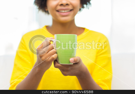 happy african american woman drinking from tea cup stock photo, people, drinks and leisure concept - close up of happy african american woman drinking tea from cup or mug at home by Syda Productions