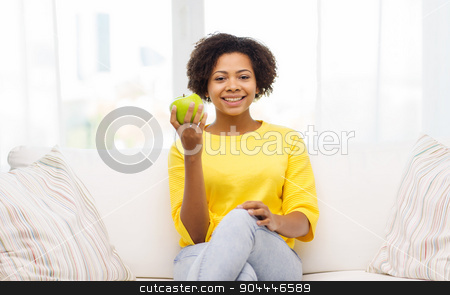 happy african american woman with green apple stock photo, people, food, healthy eating and dental care concept - happy african american young woman with green apple sitting on sofa at home by Syda Productions