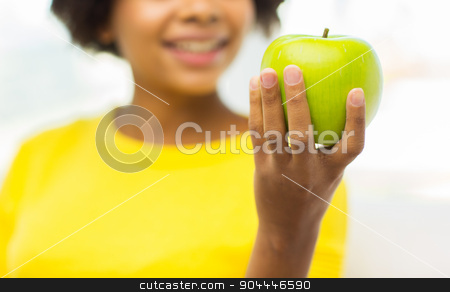 happy african american woman with green apple stock photo, people, food, healthy eating and dental care concept - close up of happy african american young woman with green apple at home by Syda Productions