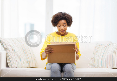 happy african young woman with parcel box at home stock photo, people, delivery, shipping and postal service concept - happy african american young woman opening cardboard box or parcel at home by Syda Productions
