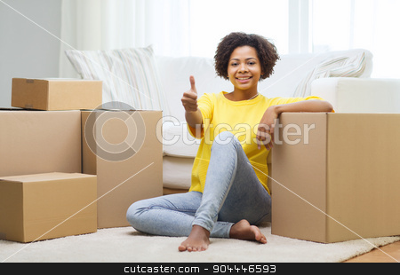 happy african woman with cardboard boxes at home stock photo, people, moving new place, gesture and repair concept - happy african american young woman with many cardboard boxes sitting on floor and showing thumbs up at home by Syda Productions