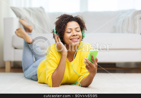 happy african woman with smartphone and headphones stock photo, people, technology and leisure concept - happy african american young woman lying on floor with smartphone and headphones listening to music at home by Syda Productions