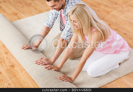 happy couple unrolling carpet or rug at home stock photo, people, repair and renovation concept - happy couple unrolling carpet or rug on floor at home by Syda Productions