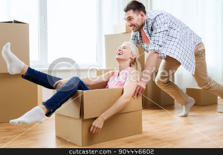 couple with cardboard boxes having fun at new home stock photo, home, people, moving and real estate concept - happy couple having fun and riding in cardboard boxes at new home by Syda Productions