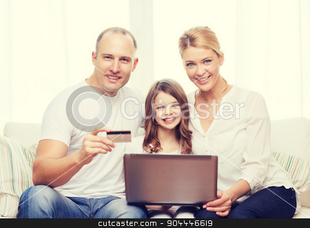 parents and girl with laptop and credit card stock photo, family, child, technology, money and home concept - smiling parents and little girl with laptop and credit card at home by Syda Productions