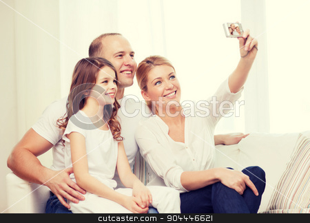 happy family with little girl making self portrait stock photo, family, child, photography and home concept - happy family with little girl making self portrait with digital camera by Syda Productions