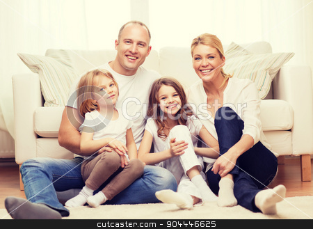 parents and two girls sitting on floor at home stock photo, family, children and home concept - smiling family with and two little girls sitting on floor at home by Syda Productions