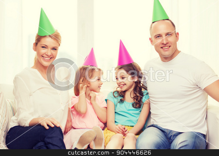 happy family with two kids in hats celebrating stock photo, celebration, family, holidays, children and birthday concept - happy family with two chldren in hats celebrating by Syda Productions