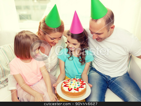 smiling family with two kids in hats with cake stock photo, celebration, family, holidays and birthday concept - happy family with two kids in hats with cake at home by Syda Productions