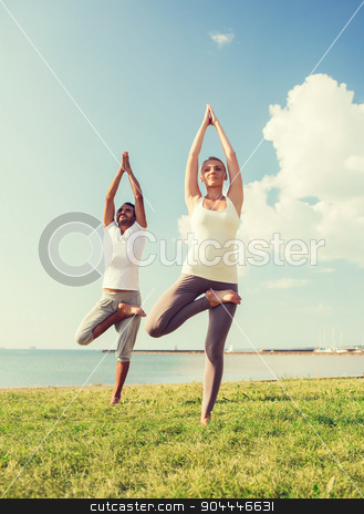 smiling couple making yoga exercises outdoors stock photo, fitness, sport, friendship and lifestyle concept - smiling couple making yoga exercises outdoors by Syda Productions
