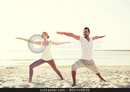 couple making yoga exercises outdoors stock photo, fitness, sport, friendship and lifestyle concept - couple making yoga exercises on beach by Syda Productions