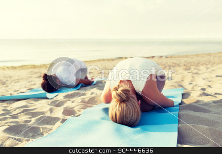 close up of couple making yoga exercises outdoors stock photo, fitness, sport, people and lifestyle concept - close up of couple making yoga exercises on mats outdoors by Syda Productions