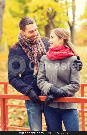smiling couple hugging on bridge in autumn park stock photo, love, relationship, family, season and people concept - smiling couple hugging on bridge in autumn park by Syda Productions