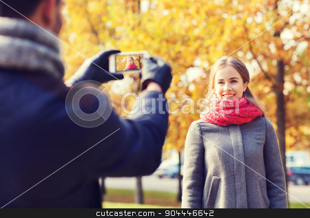 smiling couple with smartphone in autumn park stock photo, love, relationship, family and people concept - smiling couple hugging and taking selfie with smartphone in autumn park by Syda Productions