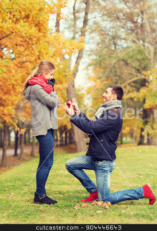smiling couple with engagement ring in gift box stock photo, love, family, autumn and people concept - smiling couple with engagement ring in small red gift box outdoors by Syda Productions
