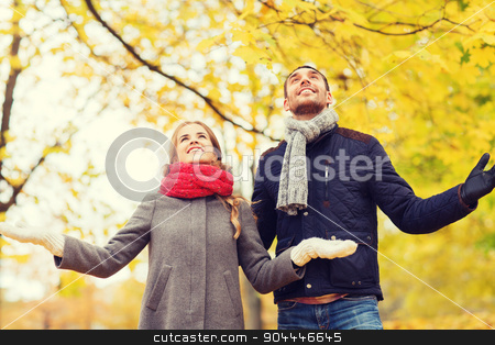 smiling couple looking up in autumn park stock photo, love, relationship, family, season and people concept - smiling couple looking up in autumn park by Syda Productions
