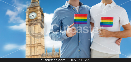 close up of male gay couple with rainbow flags stock photo, people, homosexuality, same-sex marriage, travel and love concept - close up of happy male gay couple holding rainbow flags and hugging from back over big ben tower in london background by Syda Productions