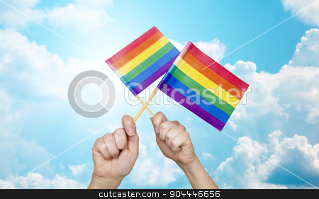 hands holding rainbow flags over sky background stock photo, people, gay pride and homosexual concept - human hands holding rainbow flags over blue sky background by Syda Productions