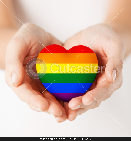 female hands with small rainbow heart stock photo, gay pride, homosexual, love and charity concept - close up of female hands holding small rainbow heart by Syda Productions