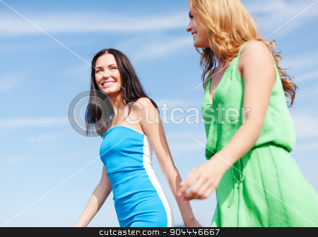 girls walking on the beach stock photo, summer holidays and vacation concept - girls walking on the beach by Syda Productions