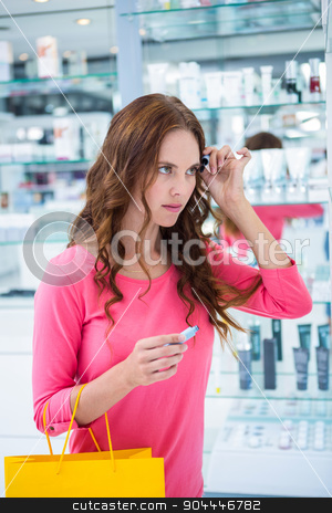 Pretty woman trying a mascara stock photo, Pretty woman trying a mascara at the pharmacy by Wavebreak Media