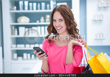 Pretty woman sending a text while shopping stock photo, Pretty woman sending a text while shopping at the pharmacy by Wavebreak Media