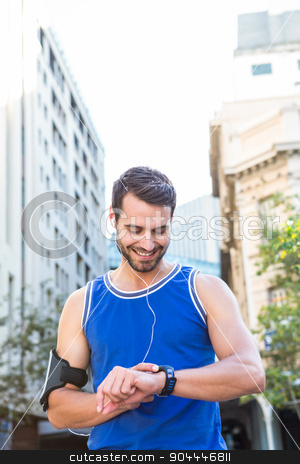 Smiling handsome athlete setting heart rate watch stock photo, Smiling handsome athlete setting heart rate watch in the city by Wavebreak Media