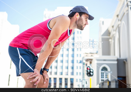 Exhausted athlete leaning forward after an effort stock photo, Exhausted athlete leaning forward after an effort on a sunny day by Wavebreak Media