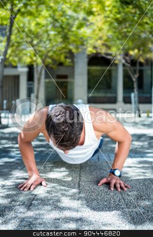 Handsome athlete doing push ups stock photo, Handsome athlete doing push ups in the city by Wavebreak Media