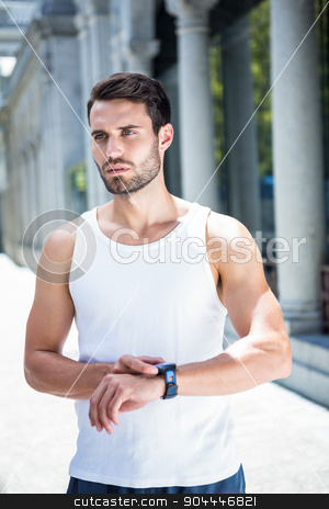 Concentrated handsome athlete checking heart rate watch stock photo, Concentrated handsome athlete checking heart rate watch in the city by Wavebreak Media