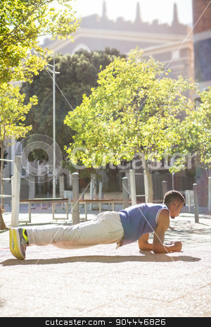 A muscular man on plank position stock photo, A muscular man on plank position on a sunny day by Wavebreak Media