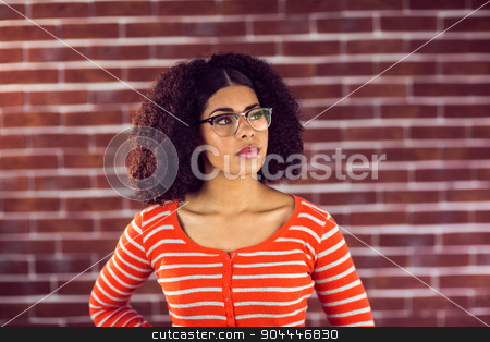 Concentrated attractive young woman stock photo, Concentrated attractive young woman against red brick background by Wavebreak Media