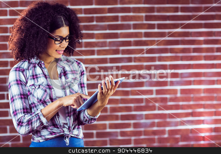 Attractive hipster smiling and using tablet stock photo, Attractive hipster smiling and using tablet against red brick background by Wavebreak Media