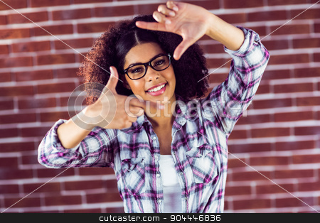 Attractive hipster taking picture with hands stock photo, Portrait of attractive hipster taking picture with hands against red brick background by Wavebreak Media