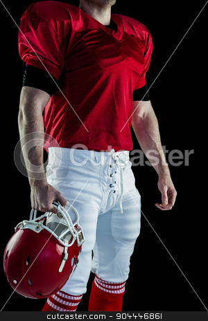American football player holding his helmet stock photo, American football player holding his helmet against black background by Wavebreak Media