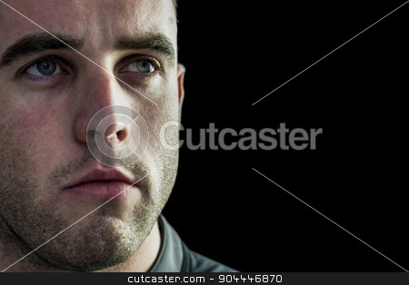 Tough rugby player looking away stock photo, Tough rugby player looking away on black background by Wavebreak Media