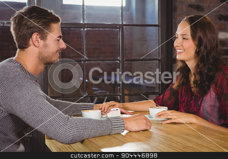 Smiling couple holding hands and having coffee together stock photo, Smiling couple holding hands and having coffee together at coffee shop by Wavebreak Media
