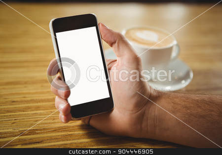 Man using her smartphone with coffee stock photo, Man using her smartphone with coffee on a wooden table by Wavebreak Media