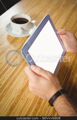 Young man having cup of coffee using tablet stock photo, Young man having cup of coffee using tablet at the cafe by Wavebreak Media