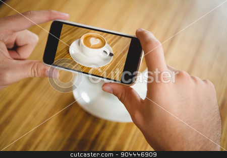 A man taking a photo of a coffee stock photo, A man taking a photo of a coffee in a cafe by Wavebreak Media