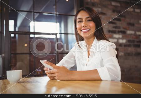 Casual businesswoman using her phones  stock photo, Casual businesswoman using her phones in a cafe by Wavebreak Media